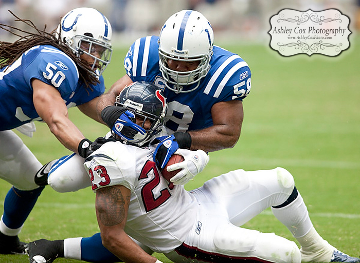 Houston Texans running back Arian Foster has his head twisted by linebackers Gary Brackett (58) and Phillip Wheeler (50) on a rush in the third quarter of a football game against the Indianapolis Colts on Sunday afternoon September 12, 2010 at Reliant Stadium in Houston. The Texans defeated the Colts 34-24 in the season opener.